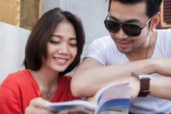 Par av den asiatiska mer unga resande mannen och kvinnan som läser en handbok Arkivbild