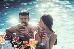 Par av den skäggiga mannen och kvinnan med coctailen och frukt i miami Sommarsemester och simning på havet Coctail på mannen arkivfoton