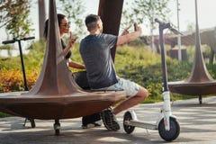 Par av den unga mannen och kvinnan som in sitter, parkerar och gör selfie fotografering för bildbyråer