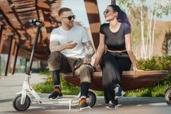 Par av den unga mannen och kvinnan som in sitter, parkerar på träbänk arkivbilder