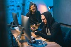 par av en hacker som räknar stulen kassa royaltyfri bild