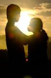 Par av förälskelse står och kramar och ögonkontakten i dimma på berget på morgonen och soluppgången bak dem Royaltyfria Foton