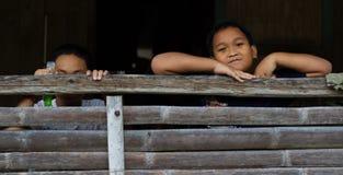 Par av fattiga byinvånarepojkar som döljer från kameran arkivbilder