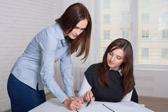 Par av flickor i formell kläder som undertecknar affärsdokument Royaltyfria Foton