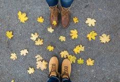 Par av fot i kängor och höstsidor Arkivfoto