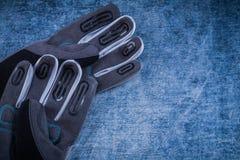 Par av funktionsdugliga handskar för tyg på skrapad metallisk yttersida Arkivfoto