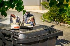 Par av gamla Adidas gymnastikskor i bra villkor på locket av soptunnan nära bostads- byggnad Gamla skor som väntar på ett nytt royaltyfri fotografi