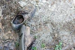 Par av gamla smutsiga använda skor Abandoned kasserade kängor som lägger i damm på jordning Armod- eller armodbegrepp Copyspace Royaltyfri Fotografi