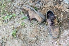 Par av gamla smutsiga använda skor Abandoned kasserade kängor som lägger i damm på jordning Armod- eller armodbegrepp Copyspace Arkivfoto