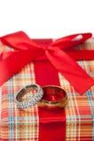 Par av guld- cirklar med apelsinrosen på den röda gåvaasken med r fotografering för bildbyråer