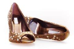 Par av guld- skor Royaltyfria Bilder