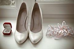 Par av guld- vigselringar, brud- skor, strumpeband Royaltyfri Bild