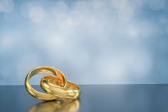 Par av guld- vigselringar på bokehbakgrund Arkivfoton