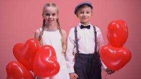 Par av gulliga ungar med röda hjärtaballonger som ler till kameran, valentindag lager videofilmer