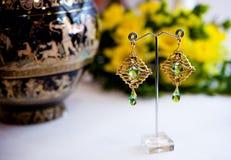 Par av härliga guld- örhängen med gemstones på den naturliga bakgrunden Arkivfoto