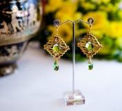 Par av härliga guld- örhängen med gemstones på den naturliga bakgrunden Arkivfoton