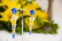 Par av härliga silverörhängen med gemstones på den naturliga bakgrunden Royaltyfri Foto