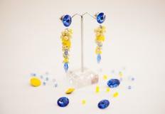 Par av härliga silverörhängen med gemstones på den naturliga bakgrunden Arkivfoto
