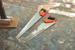 Par av handsågar på jordningen med målarfärg - garagegolvet JunkyardCouple av sågar på färgrikt smutsigt golv - Garage/Junkyard/h arkivbilder