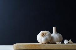 Par av hela vitlökkulor med spridda skalningar på det Wood brädet Arkivfoto