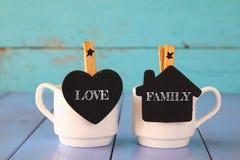 Par av koppar kaffe och små svarta tavlor med orden: FÖRÄLSKELSE FAMILJ Arkivbilder