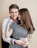 Par av lyckliga le tonåringstudenter, värme färger som har en kyss, ett livsstilfolkbegrepp, en pojke och en flicka tillsammans Royaltyfria Foton