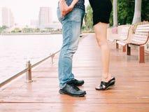 Par av mannen och kvinnliga ben under ett kyssande datum - älska och Royaltyfria Foton