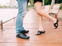 Par av mannen och kvinnliga ben under ett kyssande datum - älska och Royaltyfri Foto