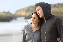 Par av melankolisk tonår som går på stranden arkivbilder