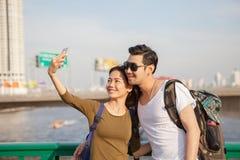 Par av mer ung man och kvinnan tar ett selfiefotografi vid sma Fotografering för Bildbyråer
