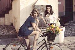 Par av modeflickor med cykeln Arkivfoto