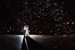 Par av nygifta personer i mörkret på bakgrunden av ljusblixten arkivbild