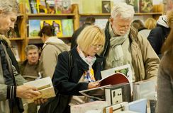 Par av pensionärer som gör val runt om böckerna av den 6th internationella festivalBOKARSENALEN Fotografering för Bildbyråer