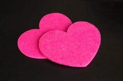 Par av rosa hjärtor mot en mörk bakgrund. Royaltyfri Foto
