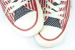 Par av skor med amerikansk stjärnor och bandgarnering Arkivbild