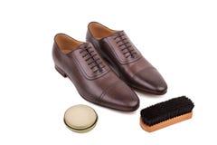 Par av skor med polermedel och borsten Arkivbild