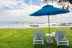 Par av soldagdrivare och ett strandparaply på en öde strand, gör perfekt semesterbegrepp arkivbilder