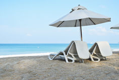 Par av soldagdrivare och ett strandparaply på stranden Royaltyfri Foto