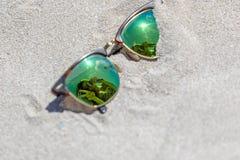 Par av solglasögon på stranden med en reflexion av ett härligt royaltyfri foto