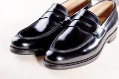 Par av stilfull dyr modern lädersvart Penny Loafers Arkivfoto