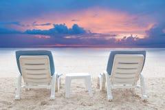 Par av stolar sätter på land på vit sand med dunkel himmelbakgrund Arkivfoto