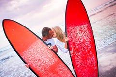 Par av surfare som kysser på kust i Indonesien Arkivbilder