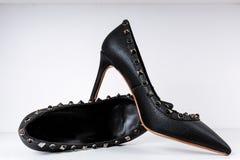Par av svarta h?g-heeled skor med spetsiga t?r som dekoreras med metallmellanl?gg mot en hylla i lagret arkivbild