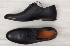 Par av svarta skor för läderman` s på grå träbakgrund Royaltyfri Fotografi