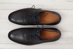 Par av svarta skor för läderman` s på grå träbakgrund Arkivbild