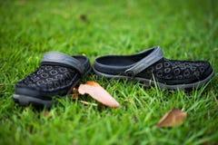 1 par av svartskor som förläggas i grönt gräs Naturligt - uppstå royaltyfri fotografi