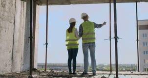 Par av teknikern eller teknikerman och kvinna med säkerhetshjälmen som rymmer mobil radiotelefonplanläggning om byggnad lager videofilmer