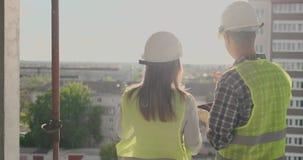 Par av teknikern eller teknikerman och kvinna med säkerhetshjälmen som rymmer mobil radiotelefonplanläggning om byggnad stock video