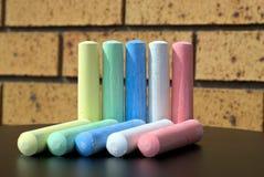 Par av tio chalks av fem olika färger på tabellen Arkivbild