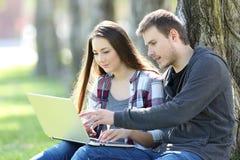 Par av tonår som direktanslutet söker som är nöjda i en bärbar dator royaltyfri fotografi
